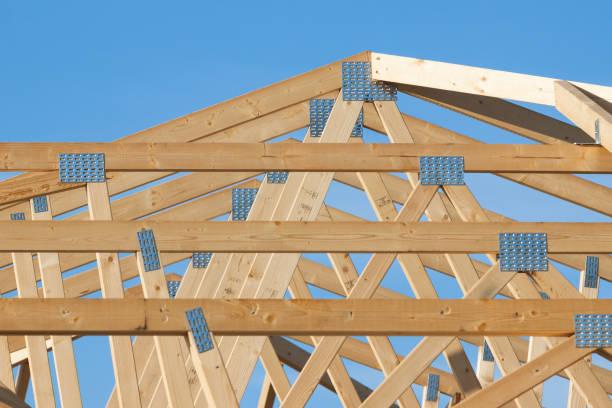 Construction d'une toiture en bois sur fond de ciel bleu