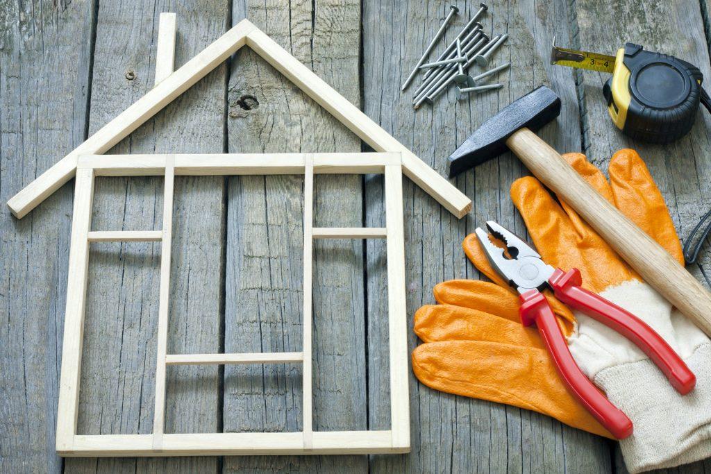 Maison en bois miniature posée sur un plancher avec des outils de bricolage à côté
